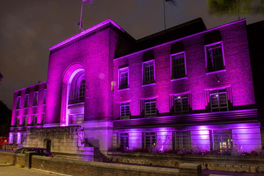 Hammersmith Town Hall at night time floodlit in purple light