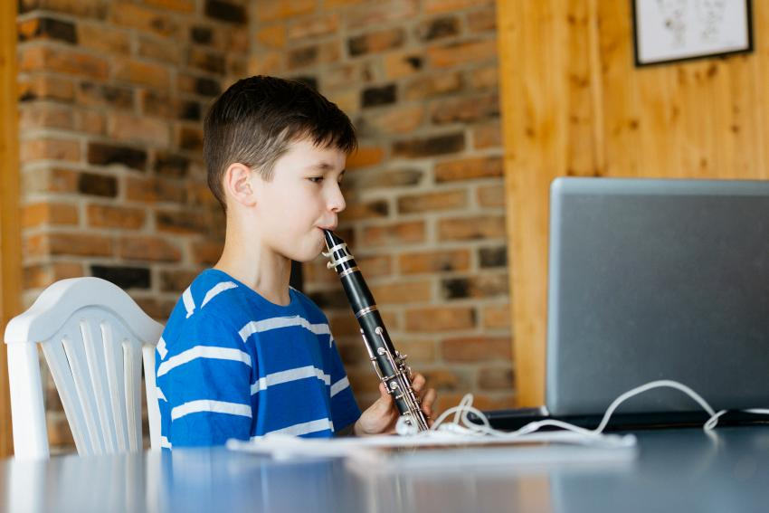 Boy playing a clarinet in front of a laptop computer