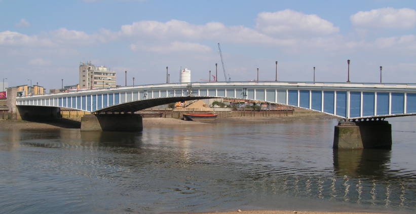 Wandsworth Bridge over the river Thames with blue sky and buildings in the background