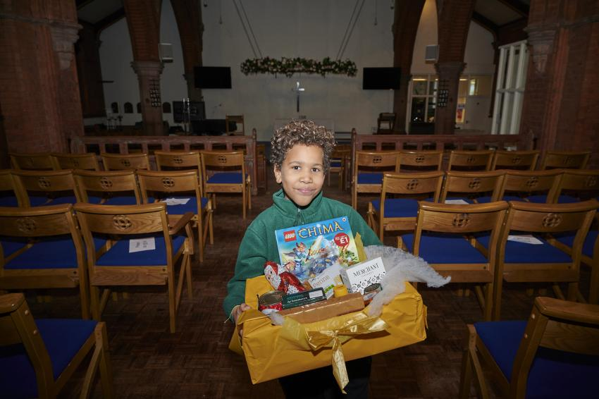 Child holding a Christmas hamper stood in the nave of St Saviour's Church