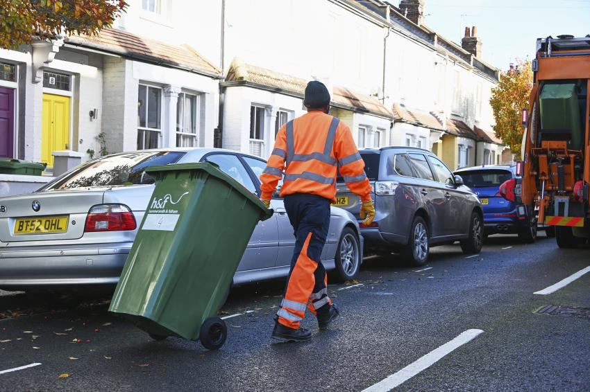 Refuse worker pulling a green recycling wheeled bin along the street