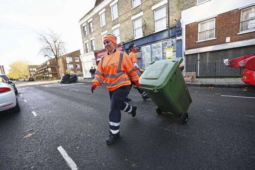 Worker pulling along one of the new wheeled bins