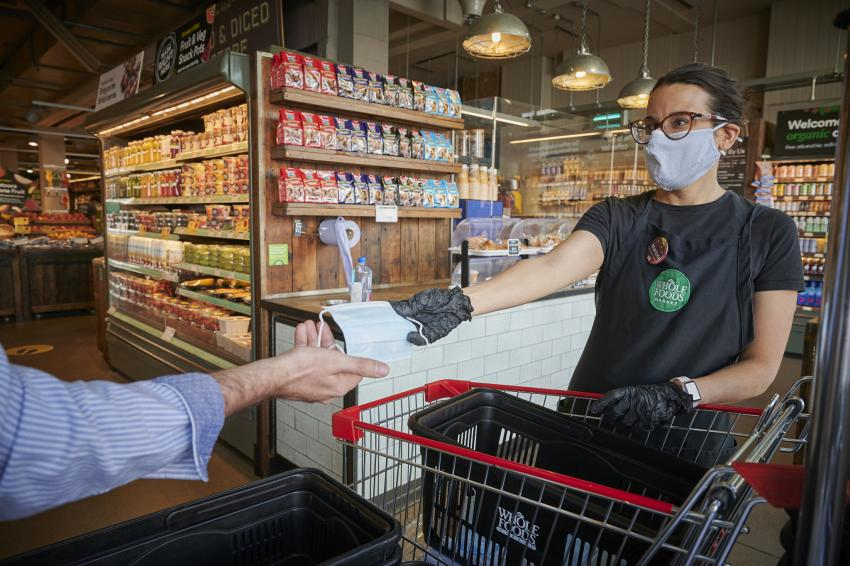 Female member of staff in Whole Foods Market, Fulham Broadway, handing face masks to customers as they enter the store