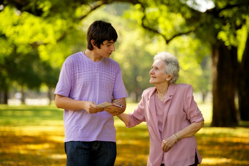 Young man walking with elderly woman