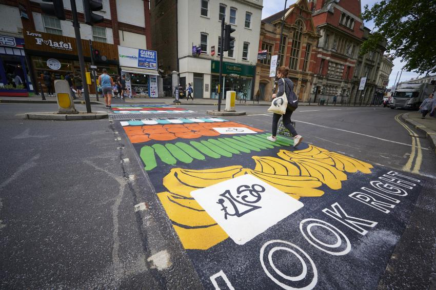 Colouful road crossing on North End Road with a pedestrian walking across
