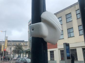White air quality sensing unit fastened to a lamp column on a high street