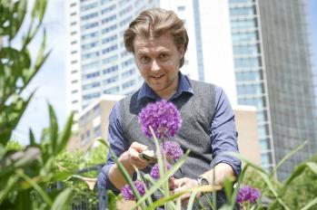 Arthur James in a garden tending a flower with a trowel