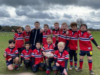 Young rugby players lined up for a team photo on a rugby pitch shirt in their strip