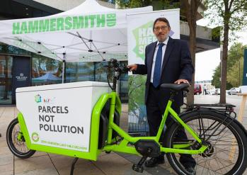 Cllr Wesley Harcourt standing behind a Parcels not Pollution branded e-cargobike