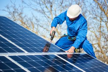 Engineer on a rooftop securing solar panels with a power drill