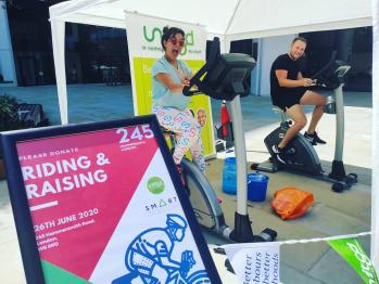 Stationery cyclists pedalling and fundraising under an awning