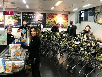 Staff stood by tills in the Westfield London Marks & Spencer store holding shopping bags