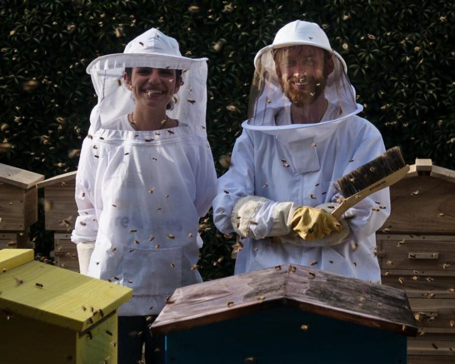 Ali Alzein and a woman stood behind beehives with bees swarming around them