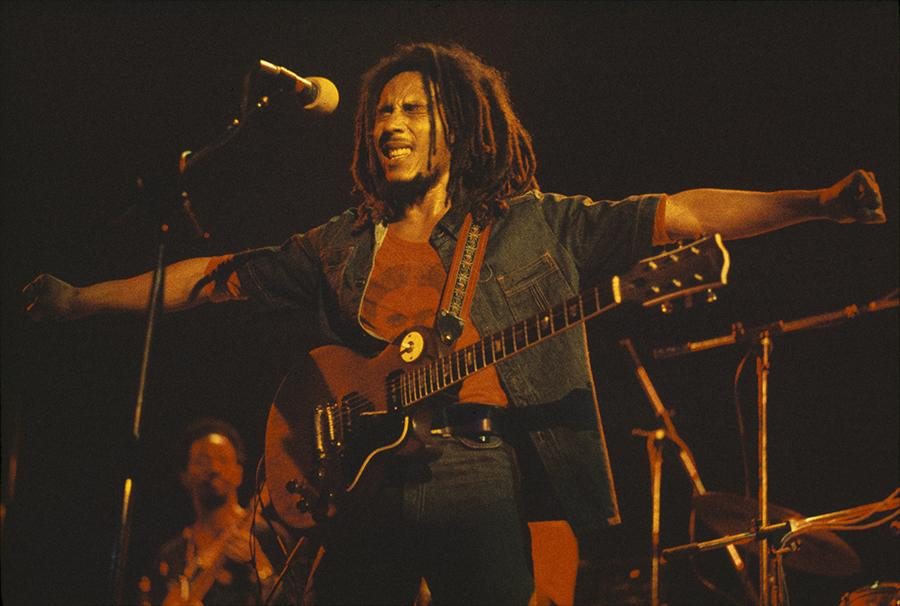 Bob Marley on stage at the Hammersmith Odeon with his arms stretched out