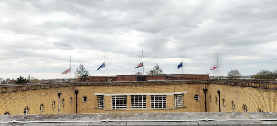 Five flags flying at half-mast over Hammersmith Town Hall with the river Thames in the distance