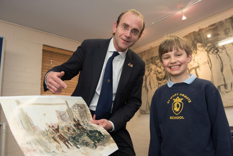 Member of staff and a young man looking at a water colour painting