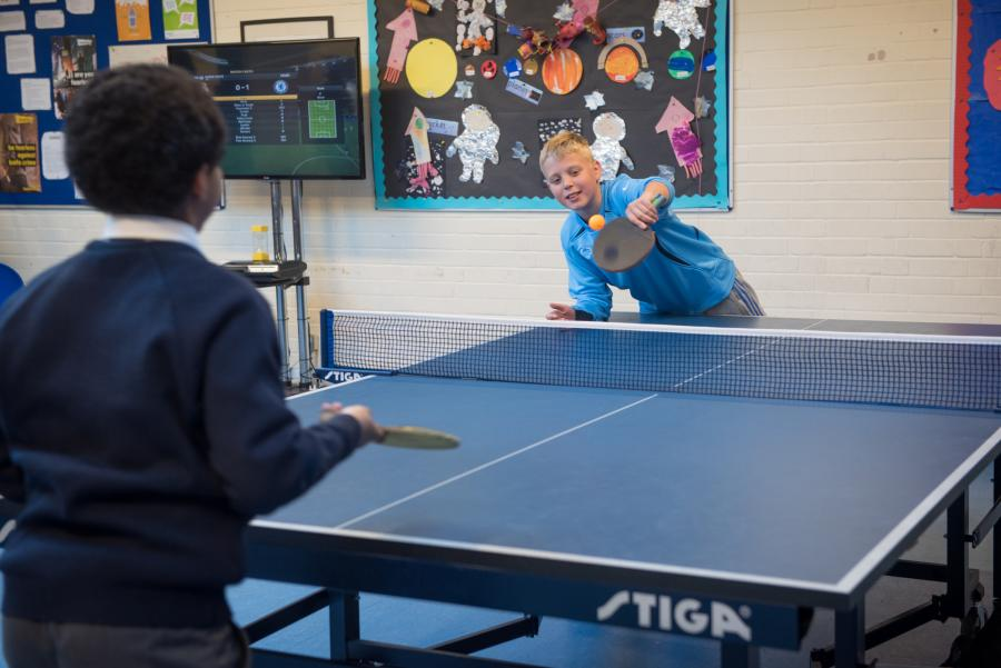 Young men playing table tennis in the Brunswick Club activity area