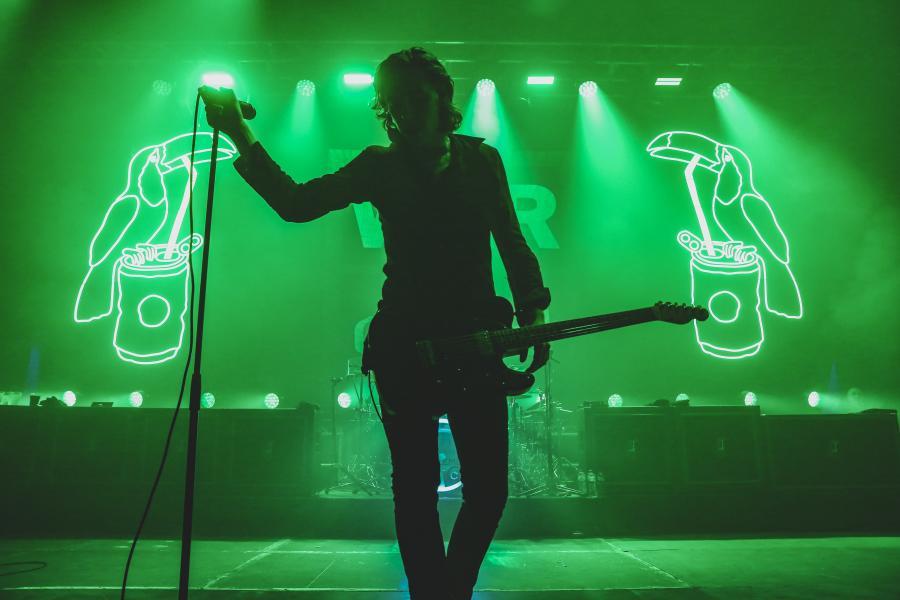 Lead singer of Catfish and the Bottlemen standing on stage in silhouette