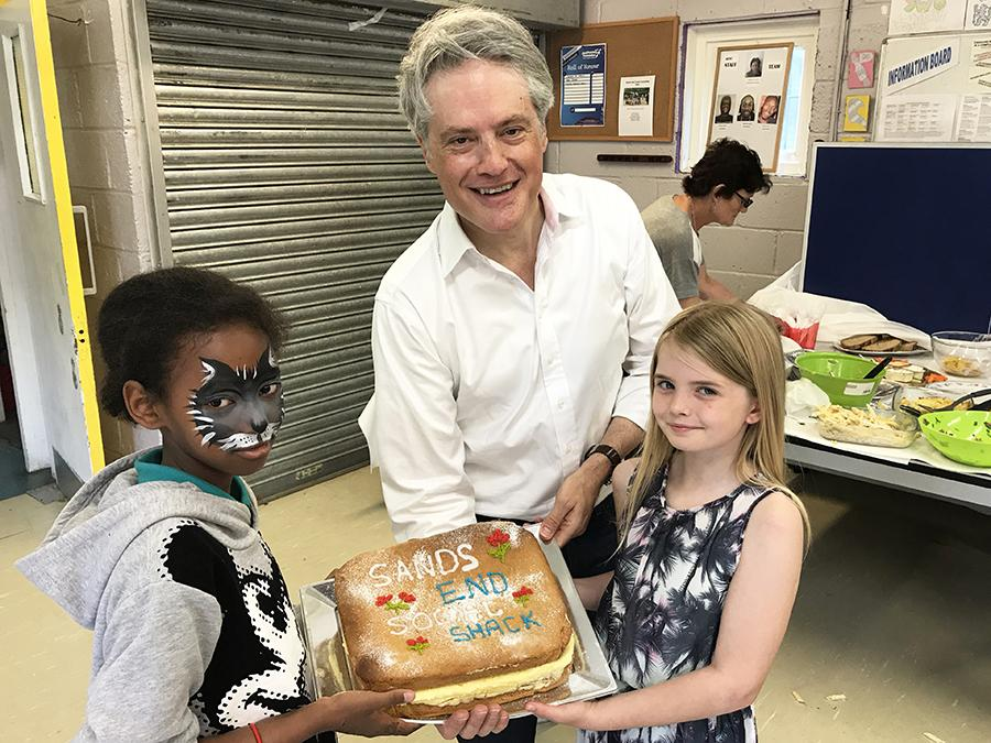 Councillor Ben Coleman and kids holding up a cake to commemorate the opening of the social shack.