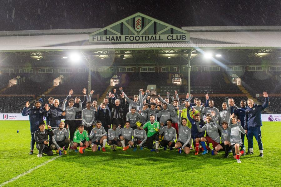 Gary Lineker with child refugees and training staff lined up on the pitch at Craven Cottage