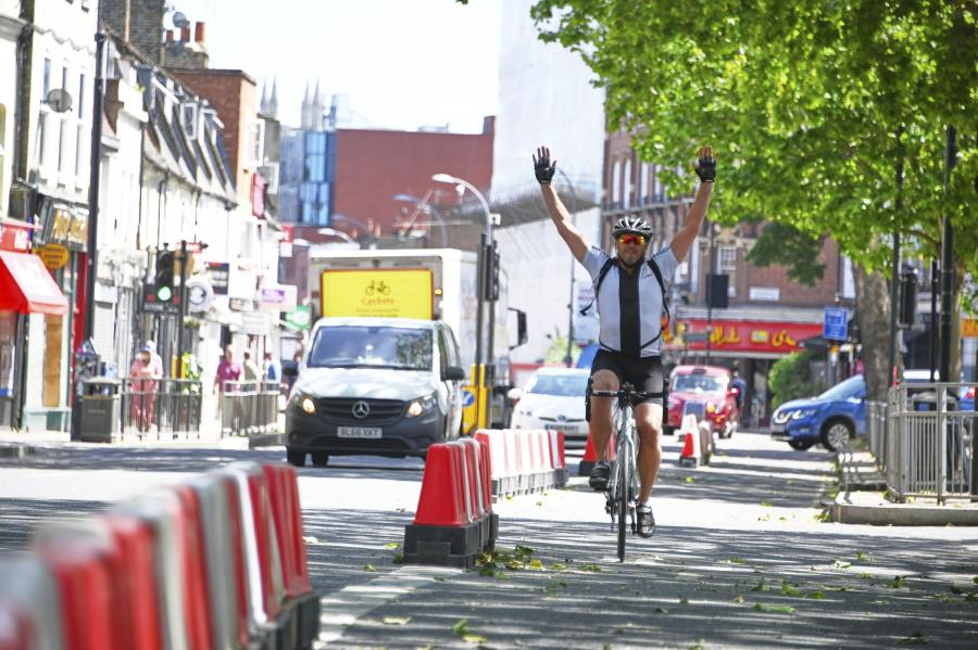 Cyclist riding inside a temporary barrier holding his arms in the air