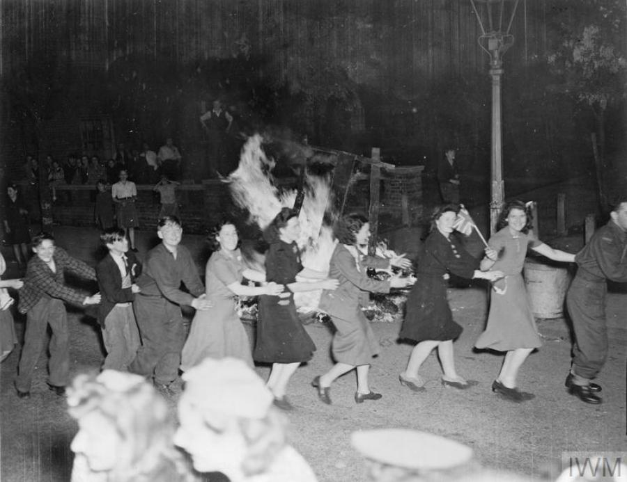 Men and women dance the conga around a bonfire in East Acton, London