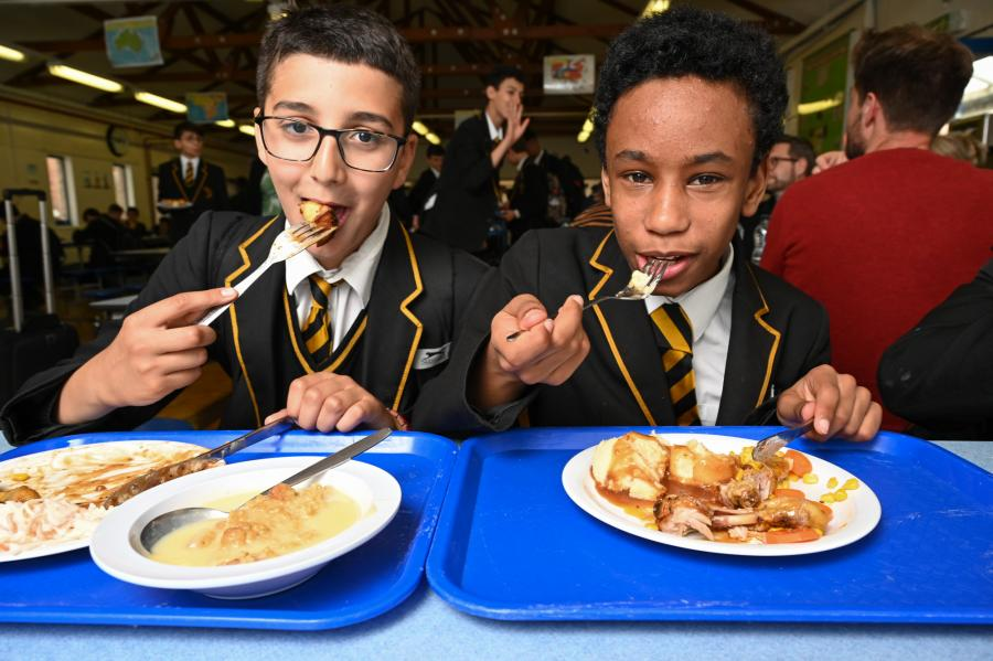 Two boys eating a school lunch in their uniforms