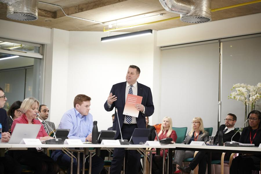 Cllr Stephen Cowan standing up at the meeting with a copy of the Independent Healthcare Commission's report in his hand