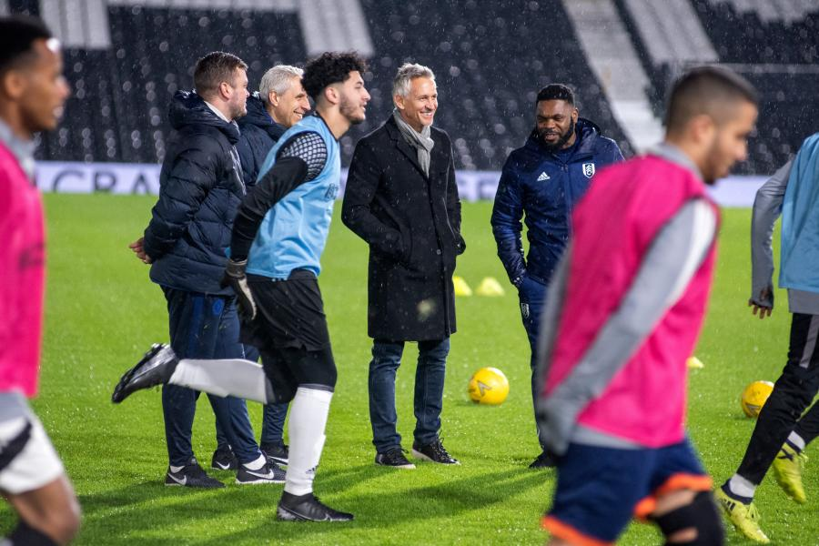 Gary Lineker with H&F child refugees on the pitch at Craven Cottage watching a training session in the rain