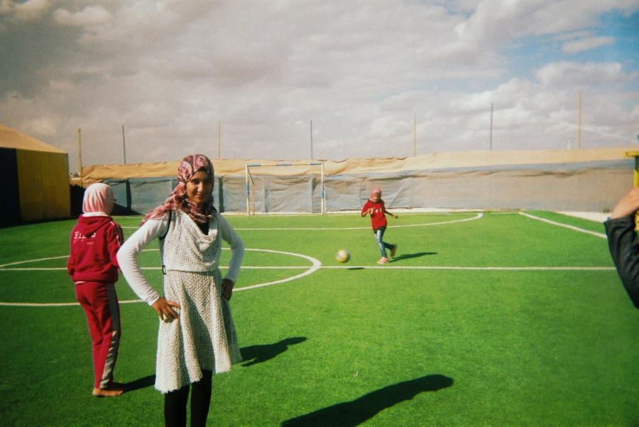 Young refugees playing football on a artificial playing surface