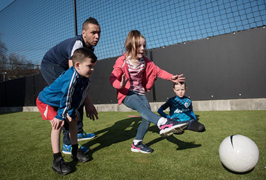 QPR coach Jason Thomas helps Abbie McKenzie, Tommy McKenzie and Charlie Busby with their shooting skills.