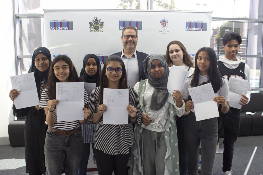 Headteacher and students at Hammersmith Academy holding up GCSE results