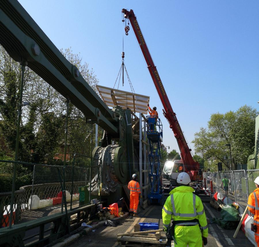 Workmen operating a crane on Hammersmith Bridge