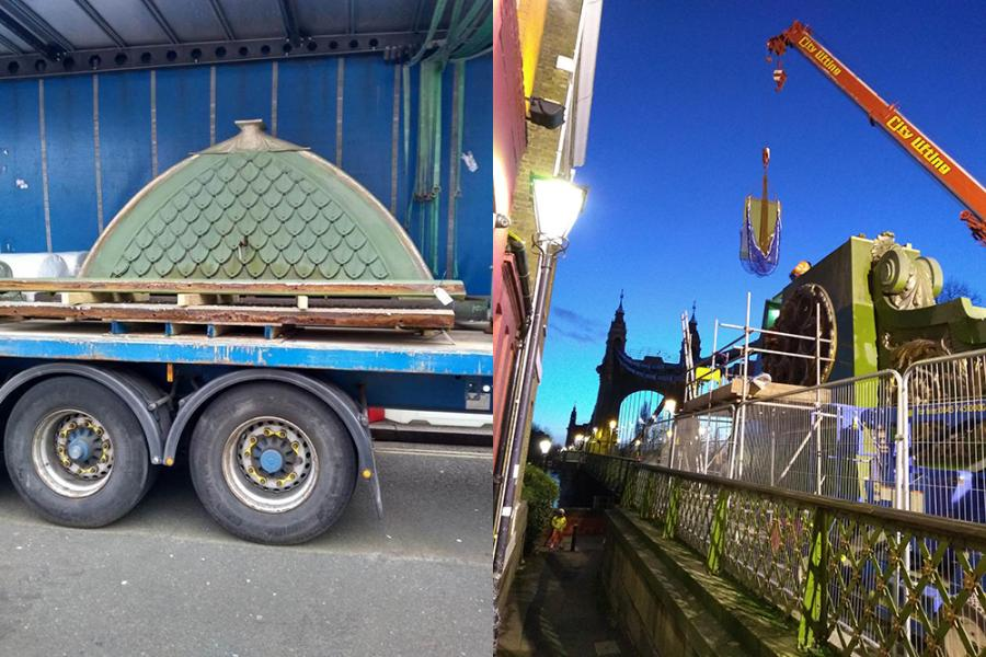 Decorative fixtures from Hammersmith Bridge on a flat-bed truck for transportation, and a crane operating at twilight on the bridge