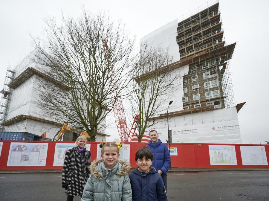 Hartopp and Lannoy Points in the background covered with scaffolding, with a group of children and adults in the foreground