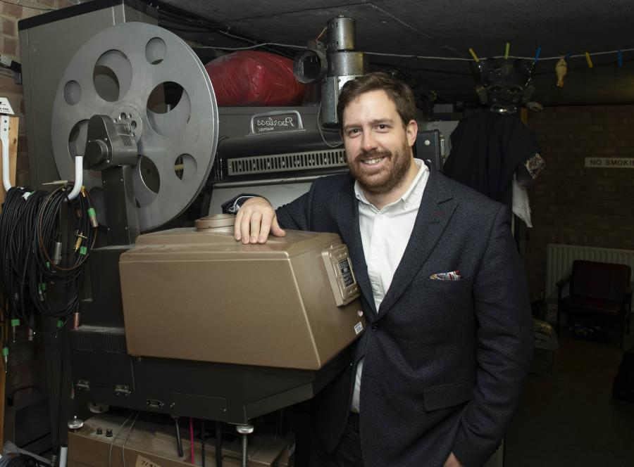 Jakub Krupa next to a film projector in the POSK projection room
