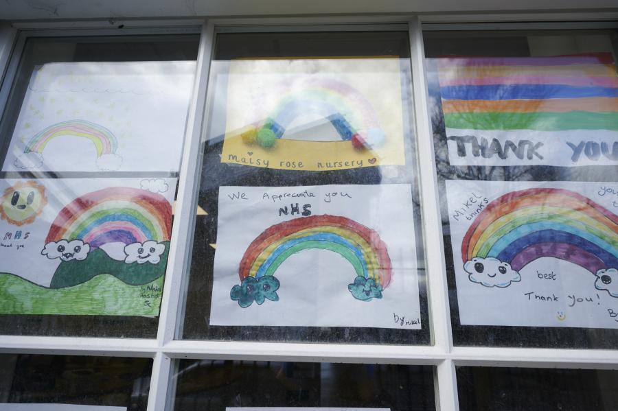 Children's rainbow art displayed on the inside of a classroom window