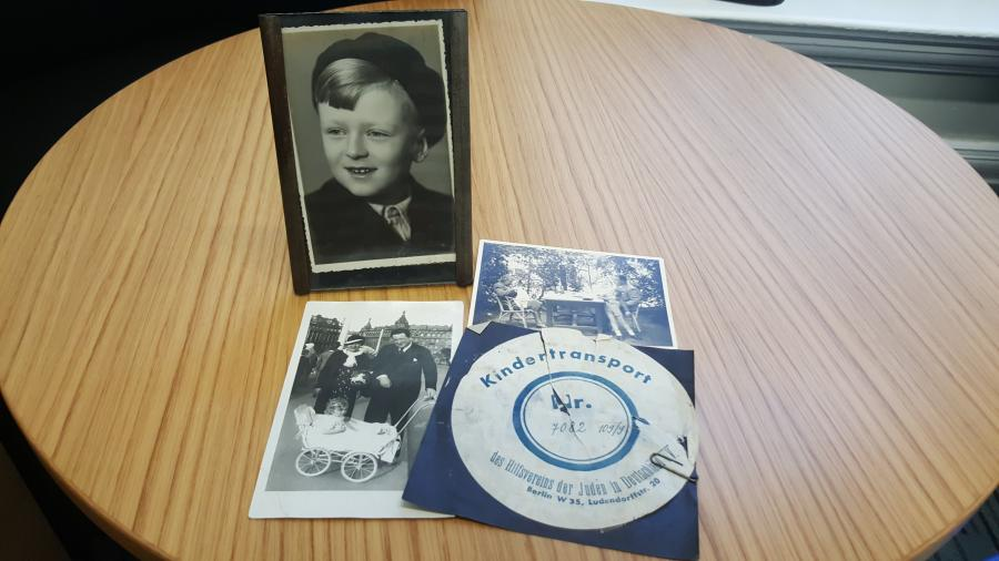 Photo of Alf Dubs as a boy in Prague on a table with other black and white family photos and kindertransport artefacts