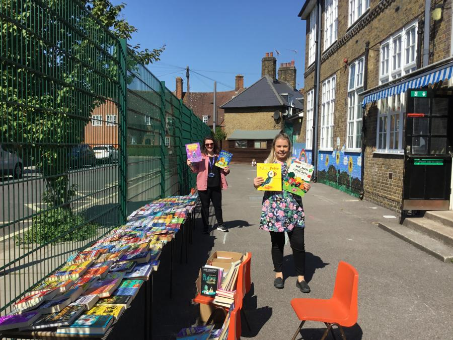 Two teachers stood in a school playground holding up books
