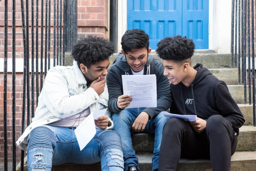 Students from Fulham College Boys sitting on steps celebrating their GCSE results