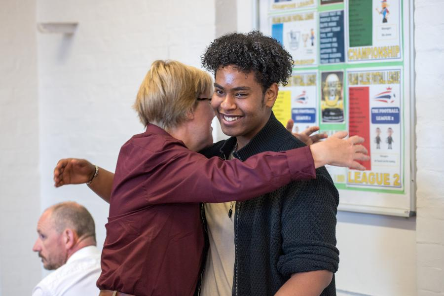 Teacher giving student a hug after GCSE results are revealed