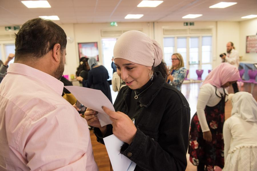 Student at Fulham Cross smiling as she reads her GCSE results