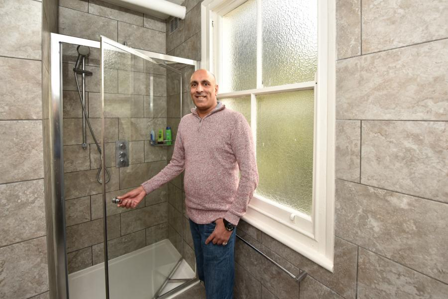 Director of Barons Court Project, Michael Angus, standing in front of rebuilt shower