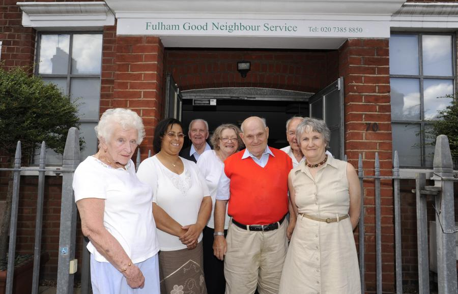 Four people standing outside the front of the Fulham Good Neighbours building