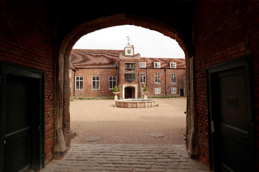 The courtyard at Fulham Palace photographed through a shady archway