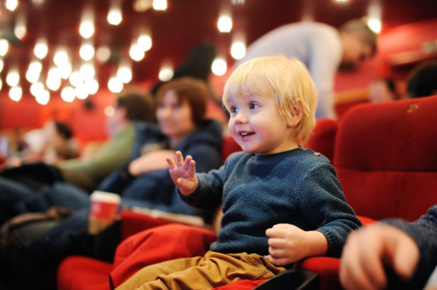 Child sitting in a red seat in a theatre auditorium