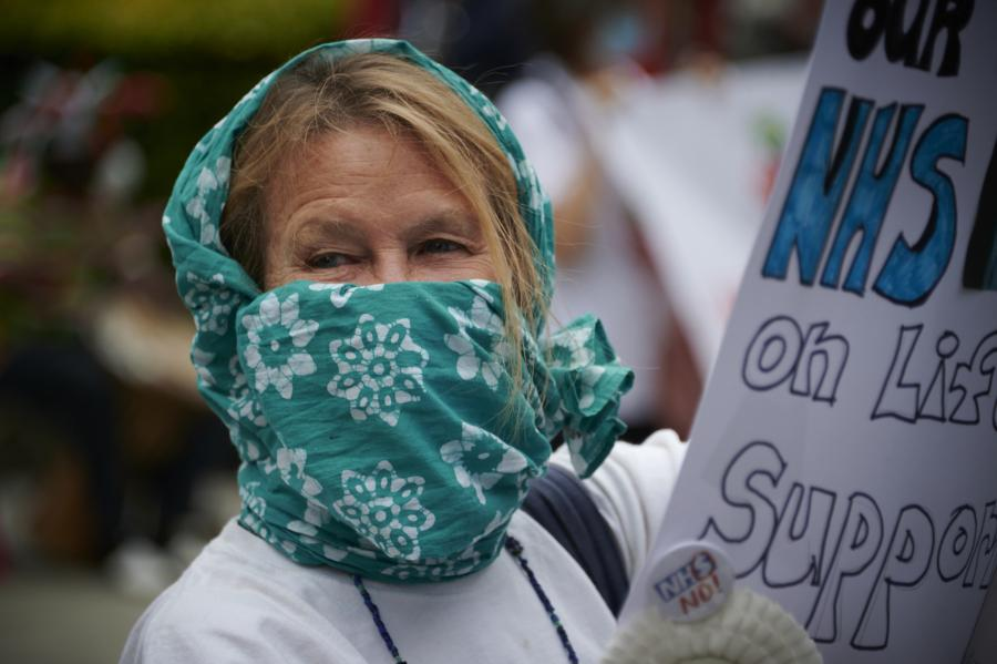 NHS supporter wearing face covering and carrying a placard