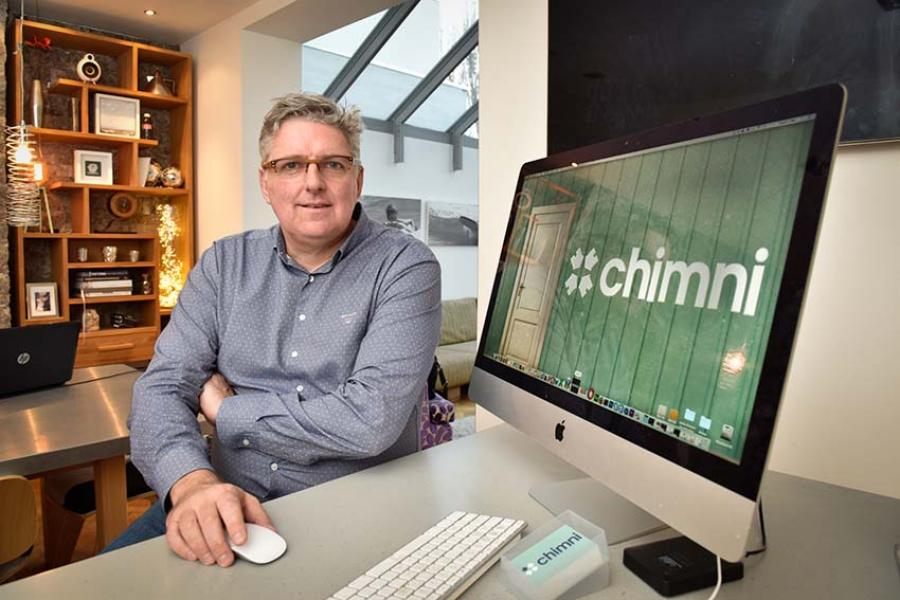 Nigel Walley sitting at his workstation and the Chimni logo showing on his Apple Mac
