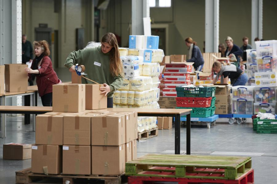 Volunteer working on Olympia London exhibition hall floor stacking cardboard boxes on a pallet