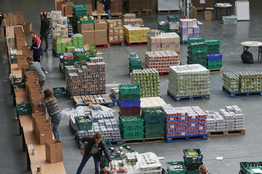 View of an exhibition hall at Olympia London with many boxes and food supplies stacked on the floor and people working around them